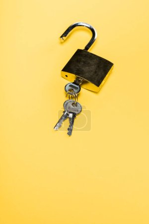 Photo for Metallic padlock with keys isolated on yellow - Royalty Free Image