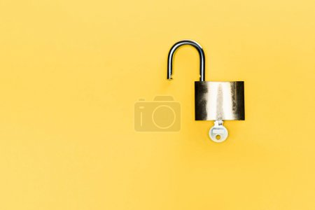 top view of metallic locker and key isolated on yellow