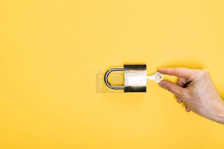 Photo pour Vue du haut de l'homme touchant la clé dans un cadenas métallique isolé en jaune - image libre de droit