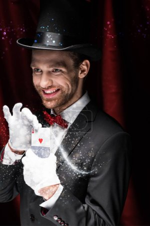 Photo pour KYIV, UKRAINE - 27 NOVEMBRE 2019 : magicien souriant tenant des cartes à jouer dans un cirque avec des rideaux rouges et une illustration lumineuse - image libre de droit