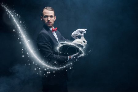 Photo for Professional magician in suit showing trick with white rabbit in hat, dark room with smoke and glowing illustration - Royalty Free Image
