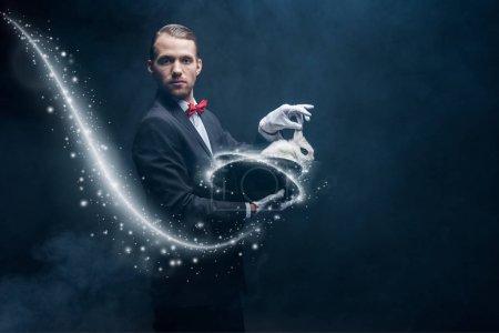 Photo pour Magicien professionnel en costume montrant tour avec lapin blanc dans le chapeau, chambre sombre avec de la fumée et illustration lumineuse - image libre de droit