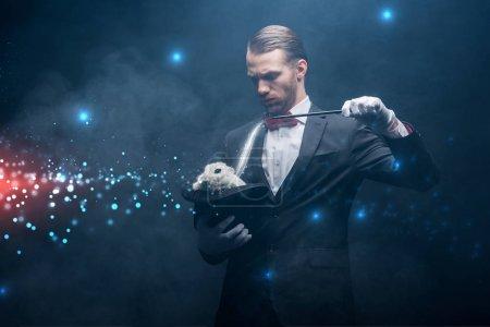 Photo pour Magicien sérieux en costume montrant tour avec baguette et lapin blanc dans le chapeau, chambre sombre avec fumée et illustration lumineuse - image libre de droit