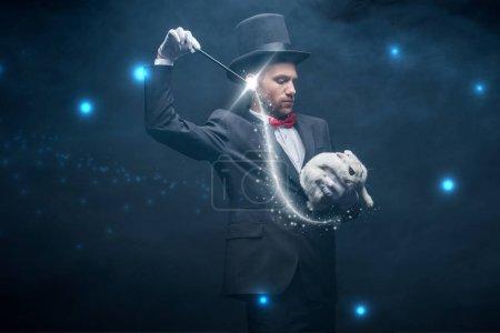 Photo pour Magicien émotionnel en costume et chapeau montrant tour avec baguette et lapin blanc, chambre sombre avec fumée et illustration lumineuse - image libre de droit