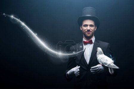 Photo pour Happy magician in hat making abracadabra with dove and wand in dark room with smoke and glowing illustration - image libre de droit