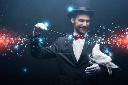 Photo pour Heureux magicien dans chapeau faire abracadabra avec colombe et baguette dans la chambre noire avec de la fumée et illustration lumineuse - image libre de droit