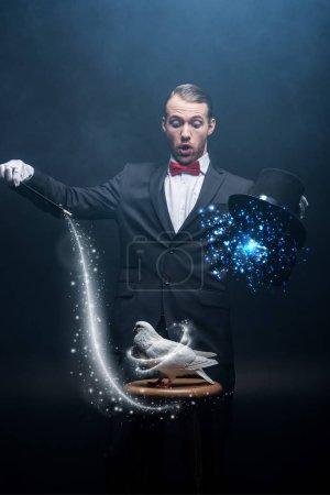 Photo pour Magicien choqué montrant un truc avec une colombe, une baguette et un chapeau dans une pièce sombre avec de la fumée et des illustrations lumineuses - image libre de droit