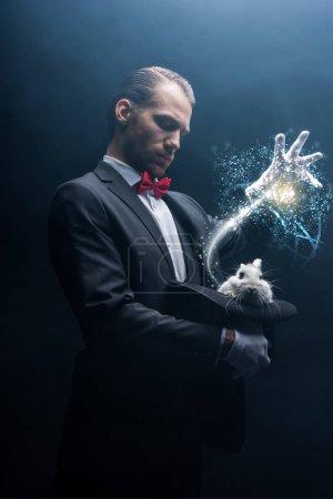 Photo pour Magicien professionnel gesticulant sur un lapin blanc dans un chapeau, pièce sombre avec de la fumée et illustration lumineuse - image libre de droit