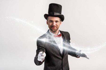 Photo pour Magicien positif en costume et chapeau tenant la baguette isolée sur gris avec illustration lumineuse - image libre de droit