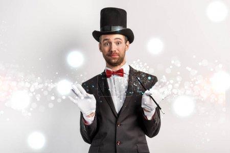 Photo pour Magicien adulte avec geste hausseur d'épaules tenant baguette sur gris avec illustration lumineuse - image libre de droit