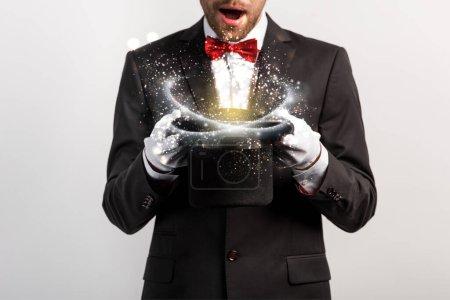 Photo pour Vue recadrée d'un magicien choqué tenant un chapeau isolé sur du gris avec une illustration lumineuse - image libre de droit