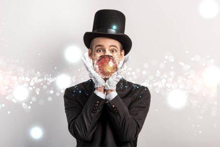 Photo pour Magicien professionnel tenant une boule magique isolée sur gris avec illustration lumineuse - image libre de droit