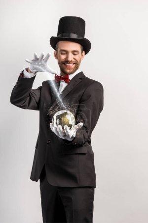 Photo pour Heureux magicien professionnel tenant boule magique isolé sur gris avec illustration lumineuse - image libre de droit