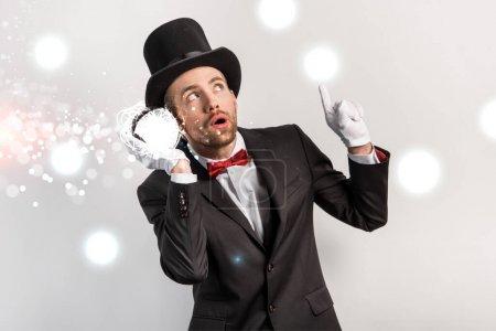 Photo pour Magicien professionnel pointant vers le haut et écoutant la boule magique isolée sur gris avec illustration lumineuse - image libre de droit