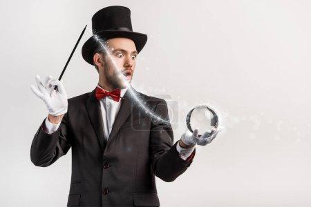 Photo pour Magicien choqué tenant baguette magique et balle isolée sur gris avec illustration lumineuse - image libre de droit