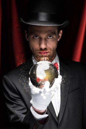 Photo pour Magicien professionnel tenant boule magique avec illustration lumineuse dans le cirque avec des rideaux rouges - image libre de droit