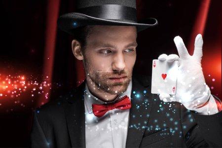 Photo pour KYIV, UKRAINE - 27 NOVEMBRE 2019 : magicien professionnel tenant des cartes à jouer dans un cirque avec des rideaux rouges et une illustration lumineuse - image libre de droit