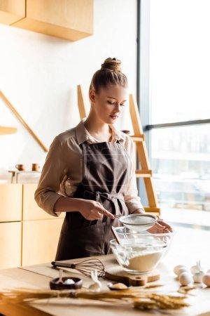 Photo pour Foyer sélectif de la fille attrayante dans le tablier tamiser la farine dans un bol près de lapins décoratifs de Pâques et les œufs - image libre de droit