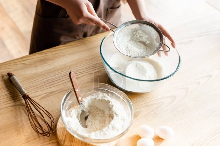 Photo for Cropped view of young woman sieving flour in glass bowl near whisk, spoon and eggs - Royalty Free Image