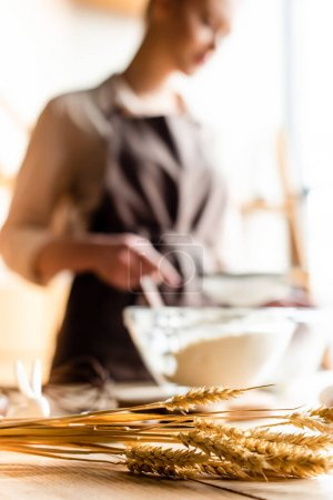 Photo for Selective focus of wheat near woman cooking in kitchen - Royalty Free Image