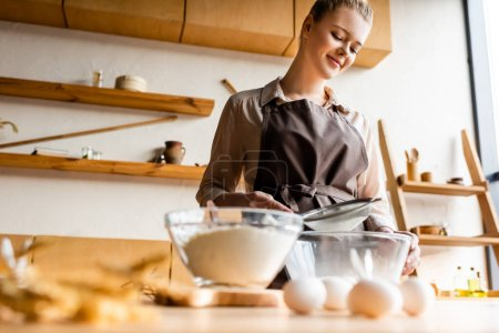 Photo for Selective focus of happy woman sieving flour in glass bowl near raw eggs on table - Royalty Free Image