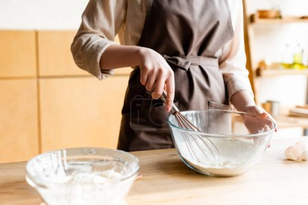 Photo for Cropped view of girl holding whisk near bowl with flour - Royalty Free Image