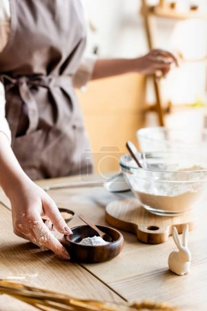 Photo for Cropped view of woman touching bowl with baking powder near decorative easter bunny and eggs - Royalty Free Image
