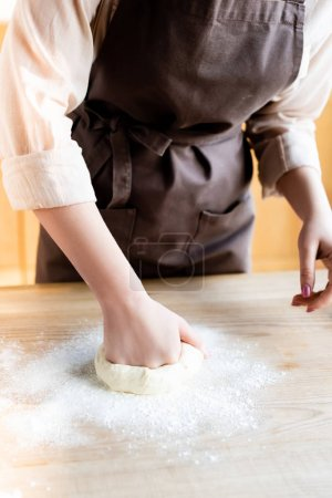 Photo for Cropped view of woman kneading dough on table - Royalty Free Image