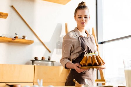 Photo for Attractive woman in apron holding baked easter cake - Royalty Free Image