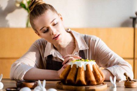 Photo pour Foyer sélectif de fille attrayante à la recherche de gâteau de Pâques savoureux - image libre de droit
