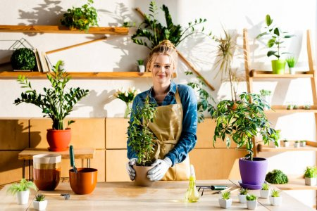 Photo for Happy girl in apron and gloves smiling near green plants - Royalty Free Image