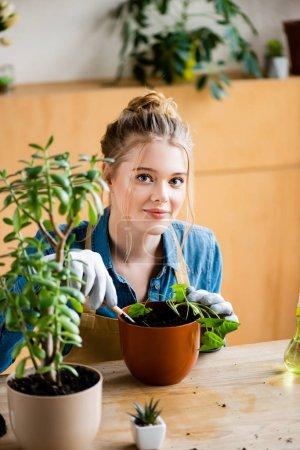 Photo pour Mise au point sélective d'une jeune fille gaie en gants tenant une petite pelle pendant la transplantation de plants en pot à fleurs - image libre de droit
