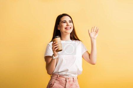 Photo pour Heureuse fille tenant café pour aller et agitant la main tout en regardant loin isolé sur jaune - image libre de droit