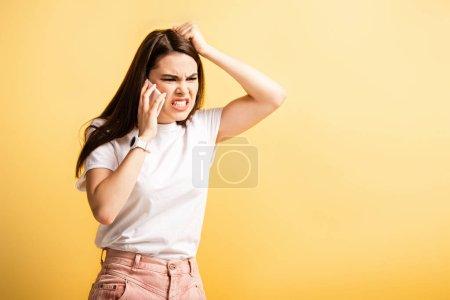 Photo pour Irritée fille toucher la tête et crier tout en parlant sur smartphone isolé sur jaune - image libre de droit