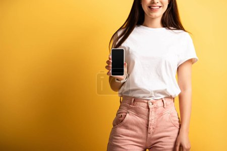vista recortada de la chica sonriente que muestra el teléfono inteligente con pantalla en blanco sobre fondo amarillo
