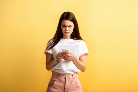 Photo for Displeased girl frowning while messaging on smartphone isolated on yellow - Royalty Free Image