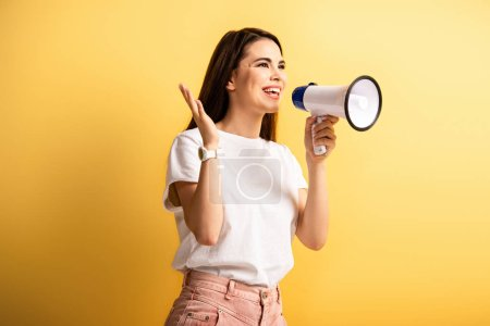 Photo pour Happy girl speaking in megaphone while standing with open arm and looking away on yellow background - image libre de droit