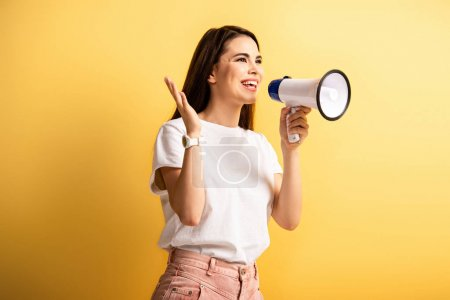 Photo for Happy girl speaking in megaphone while standing with open arm and looking away on yellow background - Royalty Free Image