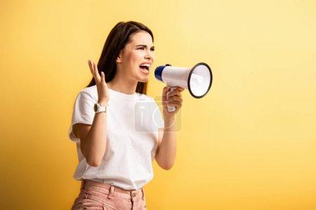 Photo pour Fille en colère criant en mégaphone tout en regardant loin sur fond jaune - image libre de droit