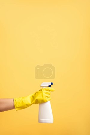 Photo for Cropped view of female hand in rubber glove with spray bottle isolated on yellow - Royalty Free Image