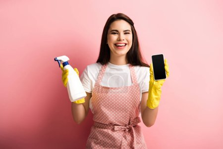 Photo pour Happy housewife in apron and rubber gloves showing smartphone with blank screen while holding spray bottle on pink background - image libre de droit