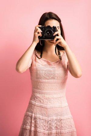Photo pour Photographe en robe élégante prenant des photos sur appareil photo numérique sur fond rose - image libre de droit