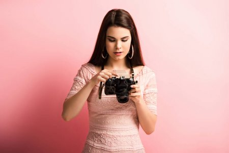 Photo pour Jolie, photographe attentif regardant appareil photo numérique sur fond rose - image libre de droit