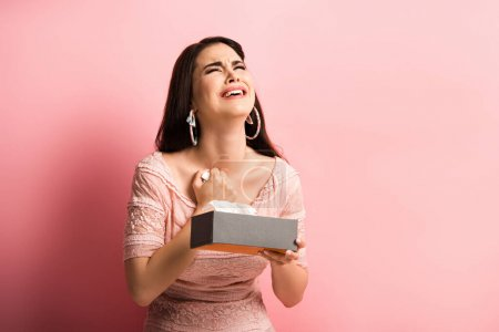 Photo for Upset girl looking up and crying while holding paper napkins on pink background - Royalty Free Image