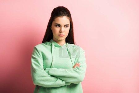 Photo pour Fille offensée regardant dehors debout, les bras croisés sur fond rose - image libre de droit