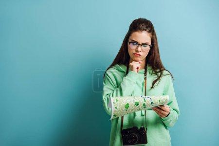 Photo pour Touriste averti avec un appareil photo numérique tenant la main près du menton tout en regardant la carte sur fond bleu - image libre de droit