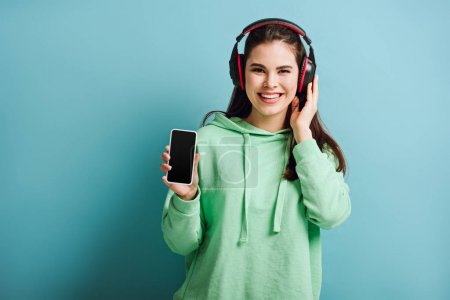 Photo for Cheerful girl in wireless headphones looking at camera while showing smartphone with blank screen on blue background - Royalty Free Image