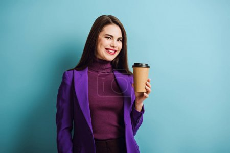 Photo for Cheerful girl looking at camera while holding coffee to go on blue background - Royalty Free Image