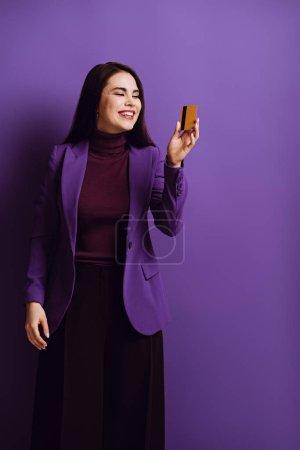 glücklich stilvolle Frau lächelt, während sie Kreditkarte auf lila Hintergrund