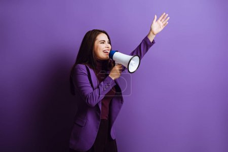 Photo for Excited young woman talking in megaphone while standing with raised hand on purple background - Royalty Free Image